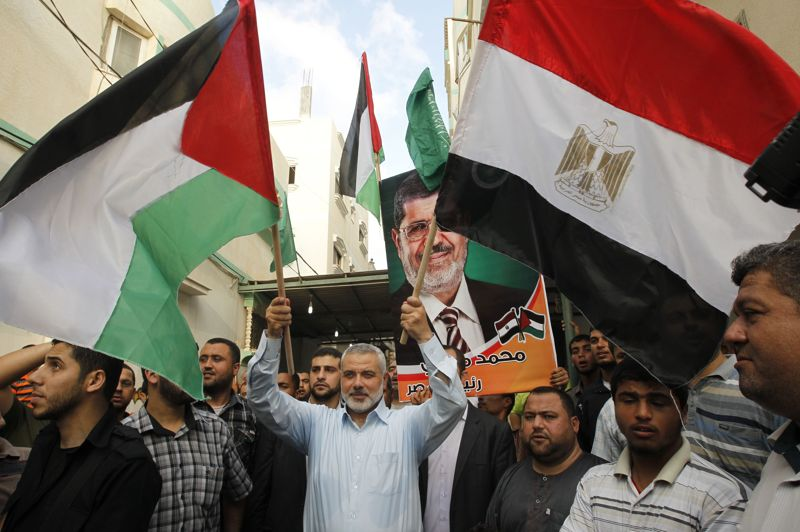 The head of Gaza's Hamas government Ismail Haniya, holds up the Palestinian and the Egyptian flags as he celebrates in Gaza City after the Muslim Brotherhood's presidential candidate Morsi was declared the winner of the Egyptian elections, on June 24, 2012 (AFP File Photo)