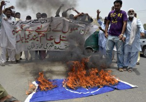 Pakistani protesters shout slogans beside a burning NATO flag during a demonstration against drone attacks in Multan on June 27, 2012.