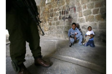 An Israeli soldier stands guard next to three Palestinian boys who were arrested for throwing stones during clashes in the West Bank city of Hebron. Hazem Bader / AFP Photo
