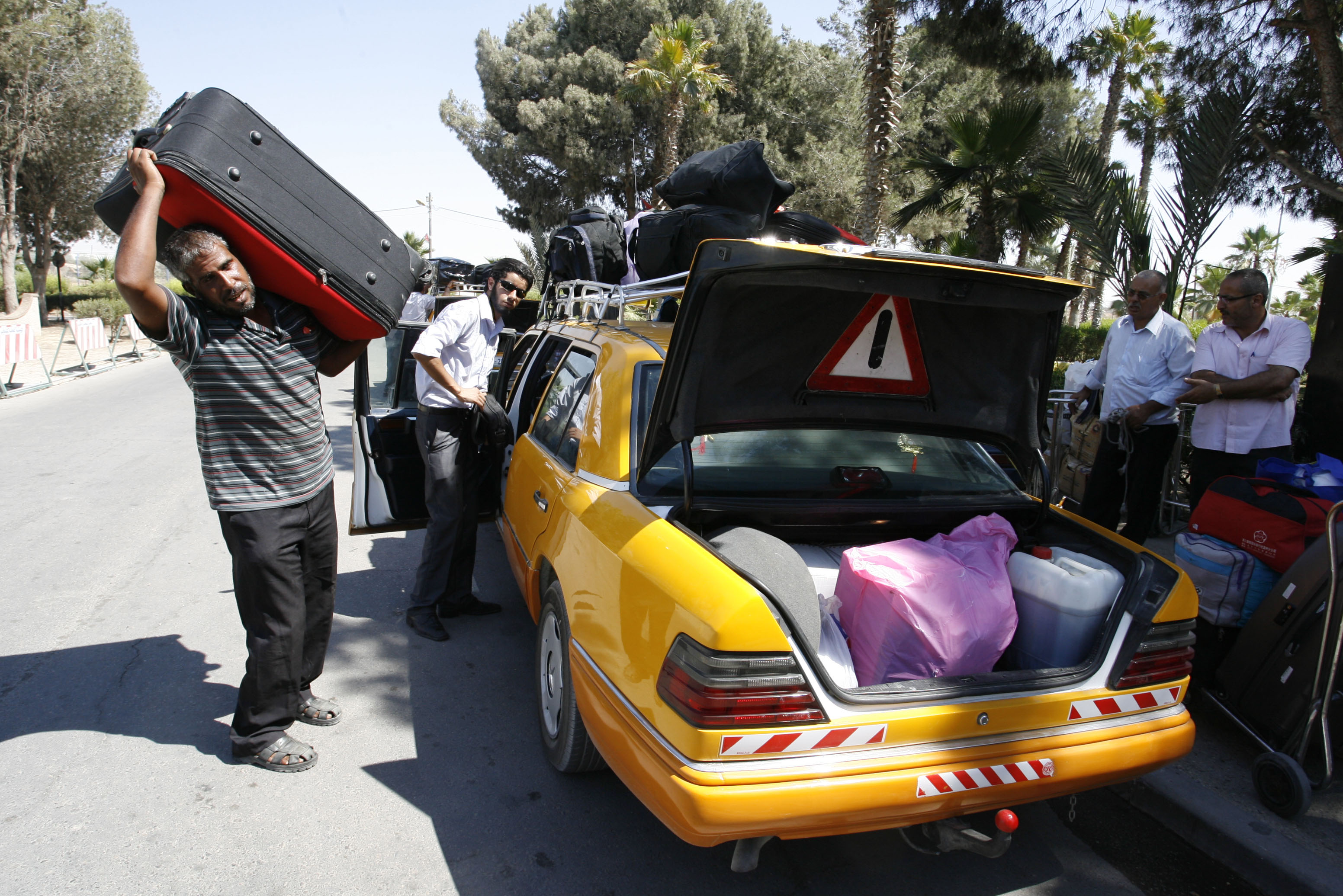 Palestinians unload their belongings from a taxi as the ready to cross to Egypt through the Rafah border crossing between the southern Gaza Strip and Egypt (photo: AFP / Said Khatib)