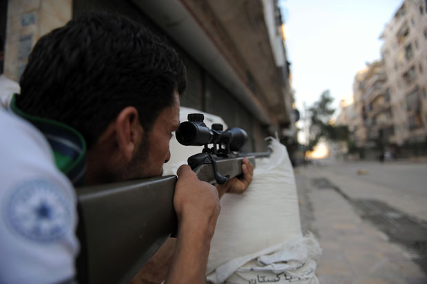A fighter from the Syrian opposition aims fire during clashes with forces loyal to President Bashar Al-Assad, in the center of Syria's restive northern city of Aleppo (photo: AFP / BULENT KILIC)
