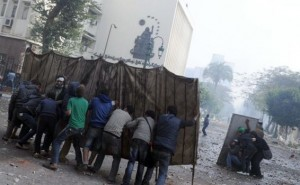 Protesters against the Prime Minister and his cabinet use makeshift shields to approach the Shura Council building during clashes with the army in December 2011 (photo: AFP/Mohamed Hossam)