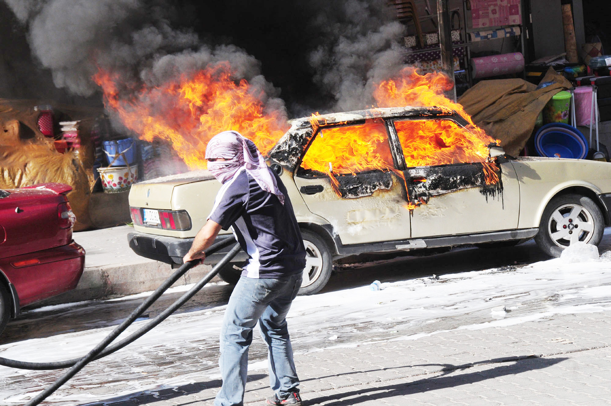 A Kurdish demonstrator stands next to a burning car as Kurdish protesters clash with Turkish police during a rally outlawed by state authoritites to demand the release of jailed rebel leader Abdullah Ocalan , on July 14, 2012, in Diyarbakir (photo: AFP)