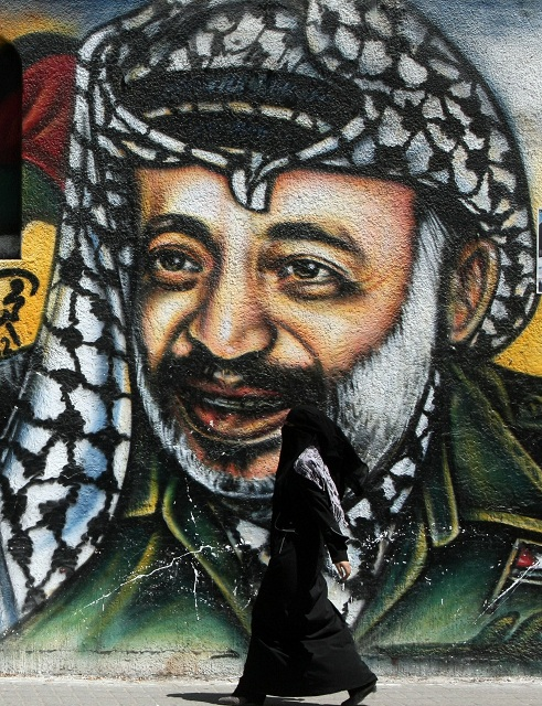 A Palestinian woman walks past a mural of late Palestinian leader Yasser Arafat in Gaza City AFP PHOTO/MAHMUD HAMS