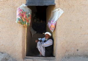 An Afghan shopkeeper sits at the door of his shop in Herat on 29 July 2012 (photo: AFP/Aref KARIMI)