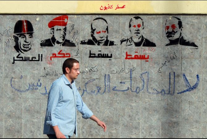 A man walks past graffiti depicting members of the military council and reading 'Down with the military rule, no to military trials for civilians' near the defense ministry in the Abasseya district of Cairo (photo: AFP/KHALED DESOUKI)