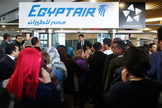 An Egypt Air worker attempts to manage a huge crowd of people looking for flights at Cairo International Airport. Civil Aviation workers are conducting a sit-in because the Civil Aviation Ministry is run by a military man (photo: AFP/Chris Hondros)