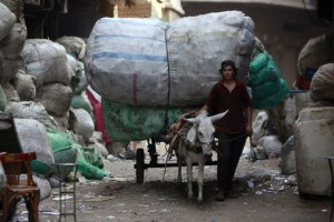 A trash collector weaves his way through old Cairo (file photo: AFP)