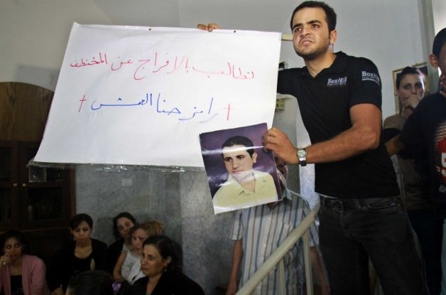 A Christian protester in Gaza city holds a picture of Ramez Abu Amash, a man who converted to Islam, according to his loved ones, through coercion (photo: AFP)