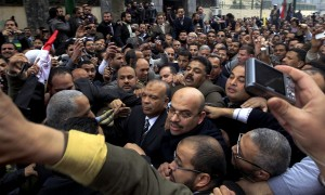 Crowds gather as secretary general of Egypt's Freedom and Justice Party (FJP) Saad al-Katatni, center, arrives to attend the newly elected parliament's first session in Cairo (photo AFP)