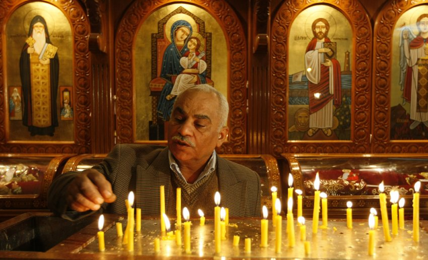 A Coptic Christian lights candles during Sunday mass in Alexandria (photo: AFP)