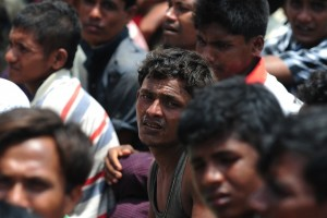 A Rohingya Muslim from Myanmar, who tried to cross the Naf river into Bangladesh to escape sectarian violence, looks on while kept under watch by Bangladeshi security officials after disembarking from an intercepted boat in Teknaf (Photo: AFP)