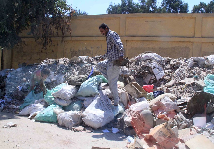 A man work to collect trash as part of Morsy's 'Clean Homeland' campaign