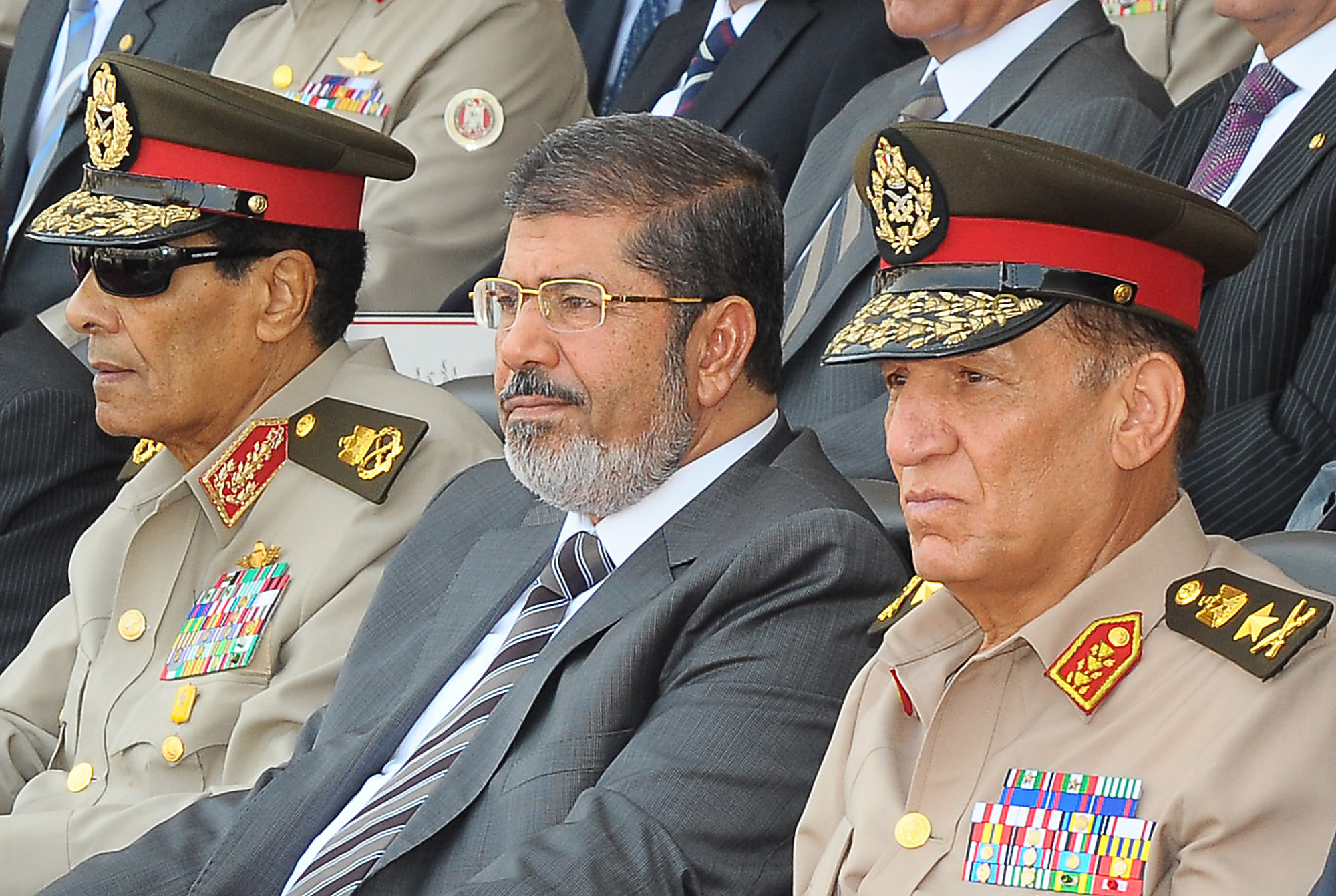 Egyptian President Mohamed Morsi (C), former head of the military council Field Marshal Mohammed Hussein Tantawi (L) and former armed forces chief Sami Anan (R) attending a graduation ceremony of military cadets in Cairo on 12 August 12, AFP PHOTO/EGYPTIAN PRESIDENCY