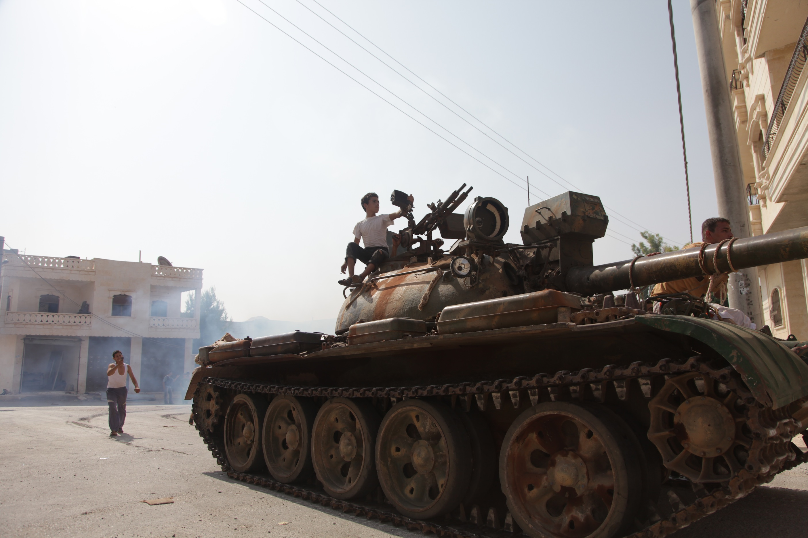 Syrian rebel fighters celebrate on top of a tank captured from the Syrian government forces at a checkpoint in the village of Anadan, about five kilometres (3.8 miles) northwest of Aleppo, on July 30 2012, after a 10-hour battle. The strategic checkpoint of Anadan secures the rebel fighters free movement between the northern city of Aleppo and Turkey, a Free Syrian Army commander and an AFP journalist said. AFP PHOTO/JUNOT DIAZ