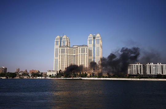 Black smoke rises from burning cars as Egyptian firefighters and bystanders try to extinguish several cars that caught on fire outside the Nile City Towers during clashes on August 2, 2012 (photo: AFP /GIANLUIGI GUERCIA)