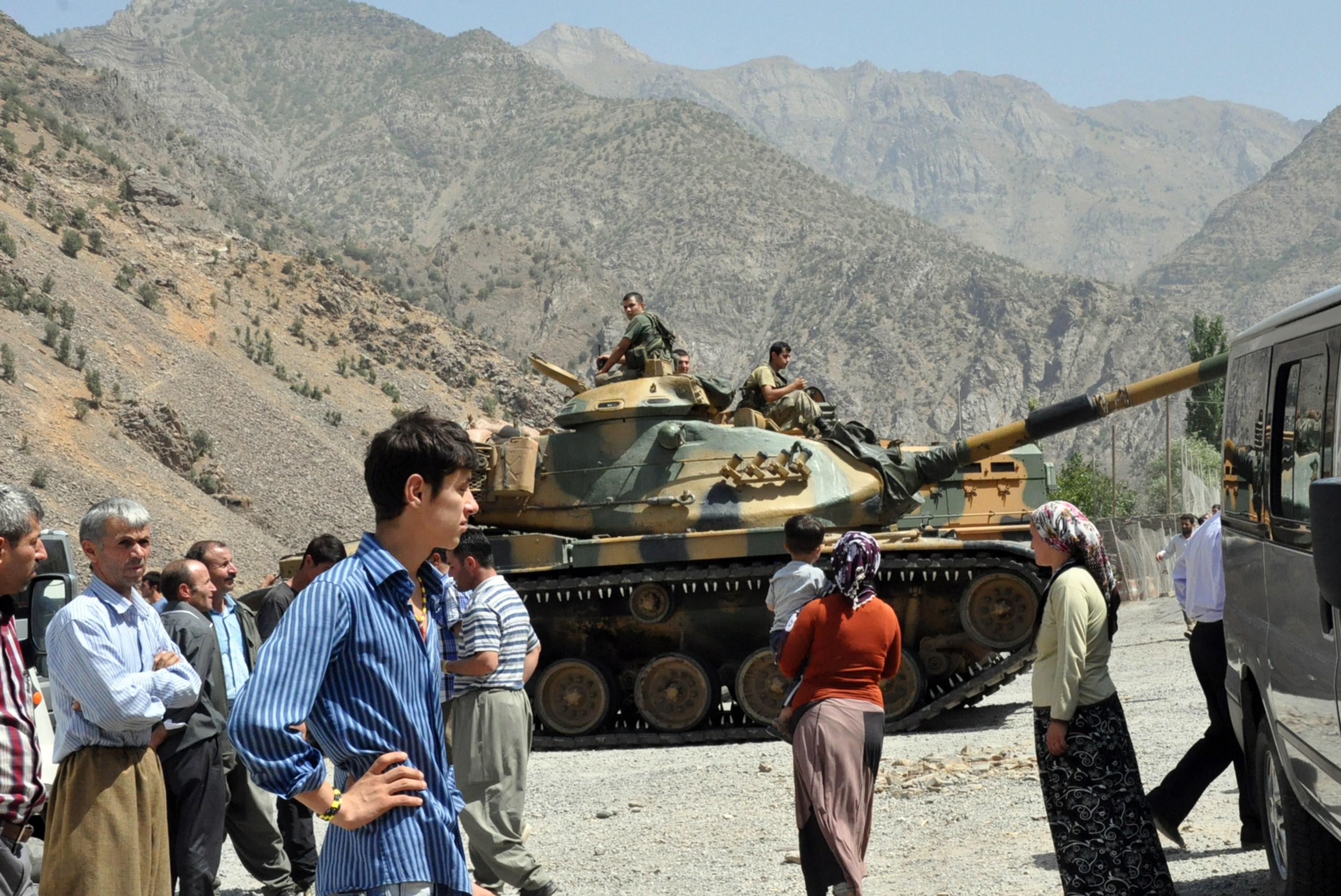 People stand near armoured vehicles of Turkish military stationed in front of Gecimli military outpost where Kurdish rebels attacked and killed 6 soldiers and 2 village guard on 5 August at Cukurca in Hakkari AFP PHOTO / STR