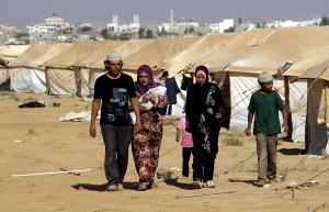 A Syrian family walk past tents at the Zaatari camp near the northern Jordanian city of Mafraq on 12 August, where French medics recently delivered tonnes of supplies and medical equipment AFP PHOTO/KHALIL MAZRAAWI