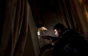 A member of the Free Syrian Army tries to spot positions held by government forces from a residential building on the outskirts of the Salaheddin neighbourhood of the northern Syrian city of Aleppo on 14 August AFP PHOTO / ACHILLEAS ZAVALLIS
