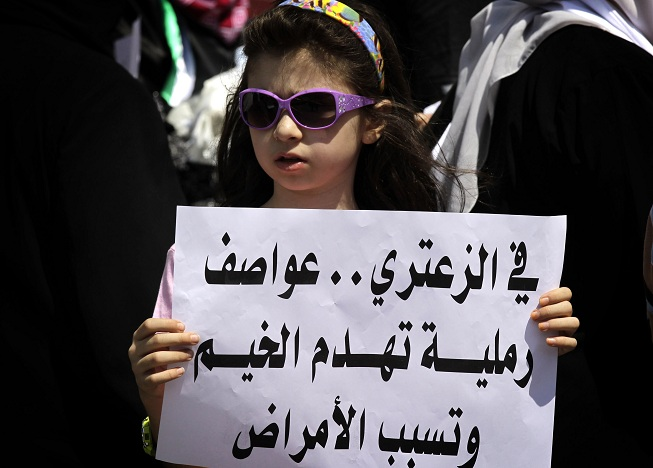 "A young girl holds a sign in Arabic that reads ""In Zaatari, sand storms destroy tents and cause diseases"" during a protest near UN offices in Amman demanding better living conditions at the Zaatari Syrian refugee camp AFP PHOTO/KHALIL MAZRAAWI"
