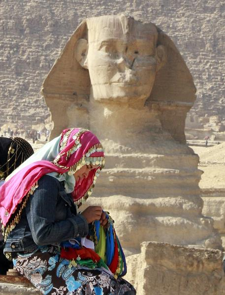 An Egyptian traditional scarf vender sews a scarf in front of the historical site of the great Sphinx in Giza (AFP Photo/Amr Nabil)