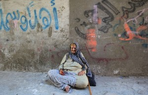 An elderly Palestinian woman sits on the ground outside her home at Al-Shati refugee camp in Gaza City AFP PHOTO / MAHMUD HAMS