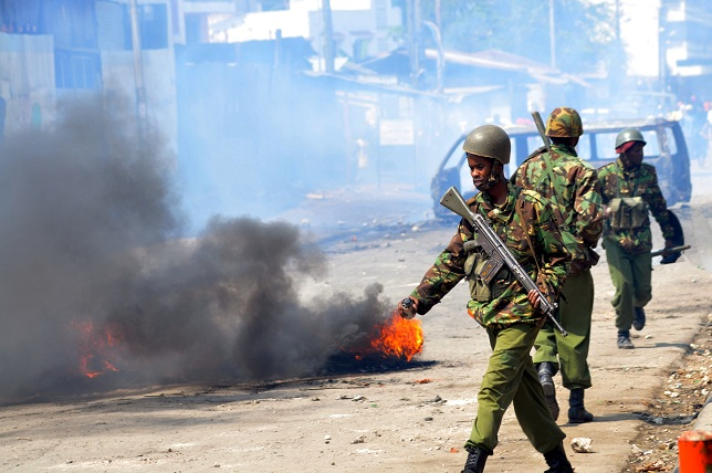 Kenyan paramilitary police walk past burning tyres in Kenya's port city of Mombasa during a second day of clashes after the killing of an extremist cleric linked to Al-Qaeda-allied Shebab militants AFP PHOTO/STRINGER