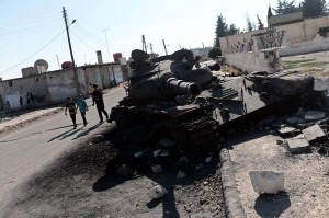 Despite Morsy's efforts to form a Quartet to solve the Syrian crisis the fighting continues. Syrian children walk past a grounded army tank in the northern town of Azaz on 23 August AFP PHOTO/ ARIS MESSINIS