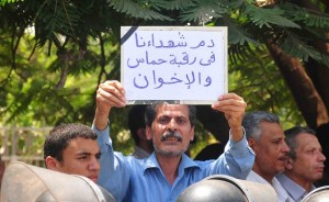 Protester holds a sign at the funeral of the soldiers killed in the Sinai, which literally reads 'The blood of the martyrs is on the necks of Hamas and the Brotherhood' blaming the deaths of the soldiers on Hamas and the Muslim Brotherhood organizations.(Photo by Hassan Ibrahim)