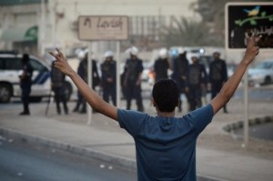 "A Bahraini Shiite protester flashes a ""V for victory"" sign at riot police in June 2012 (AFP Photo)"
