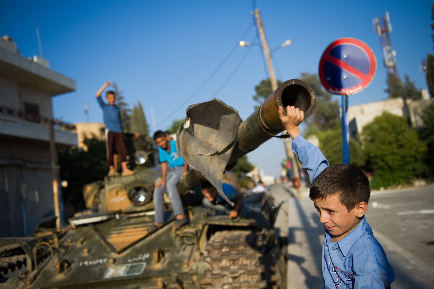 A Syrian boy plays with a tank in the town of Azaz, north of Aleppo, on 11 August AFP PHOTO / PHIL MOORE