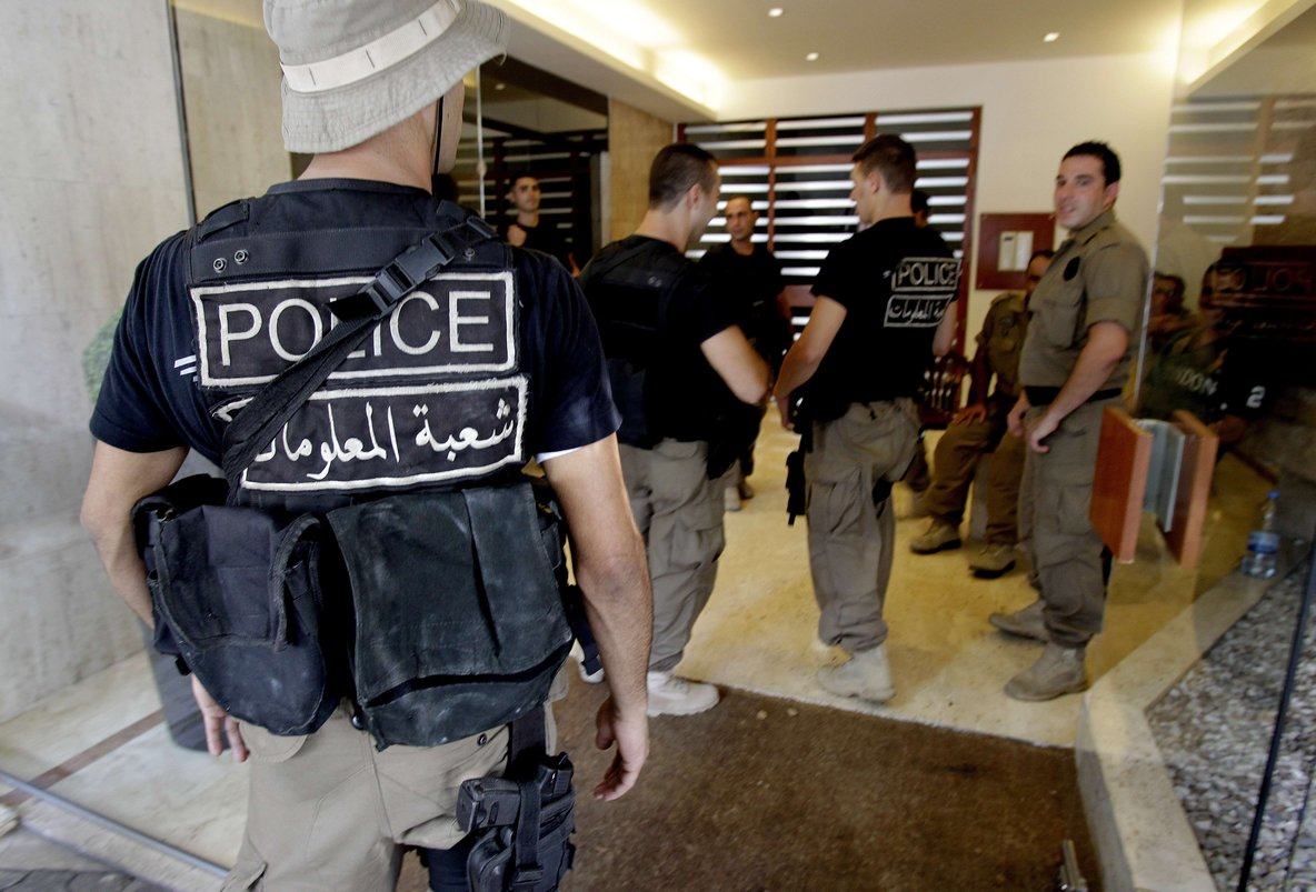 Lebanese policemen stand guard at the entrance of a residential building where former government minister Michel Samaha resides in Beirut on August 9, 2012. AFP PHOTO / ANWAR AMRO