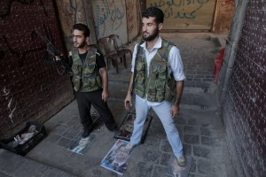 Syrian rebels stand on pictures of Syrian President Bashar Al-Assad as they take position in the northern city of Aleppo on August 3, 2012 (AFP PHOTO/AHMAD GHARABLI)