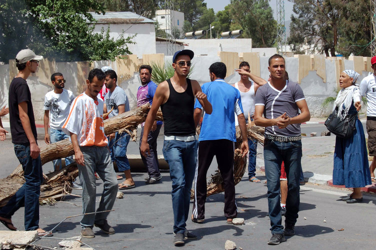 Residents of Kasserine in western Tunisia blocking a road in the centre of the city with a tree during anti-government protests (AFP PHOTO / Abderrazek)
