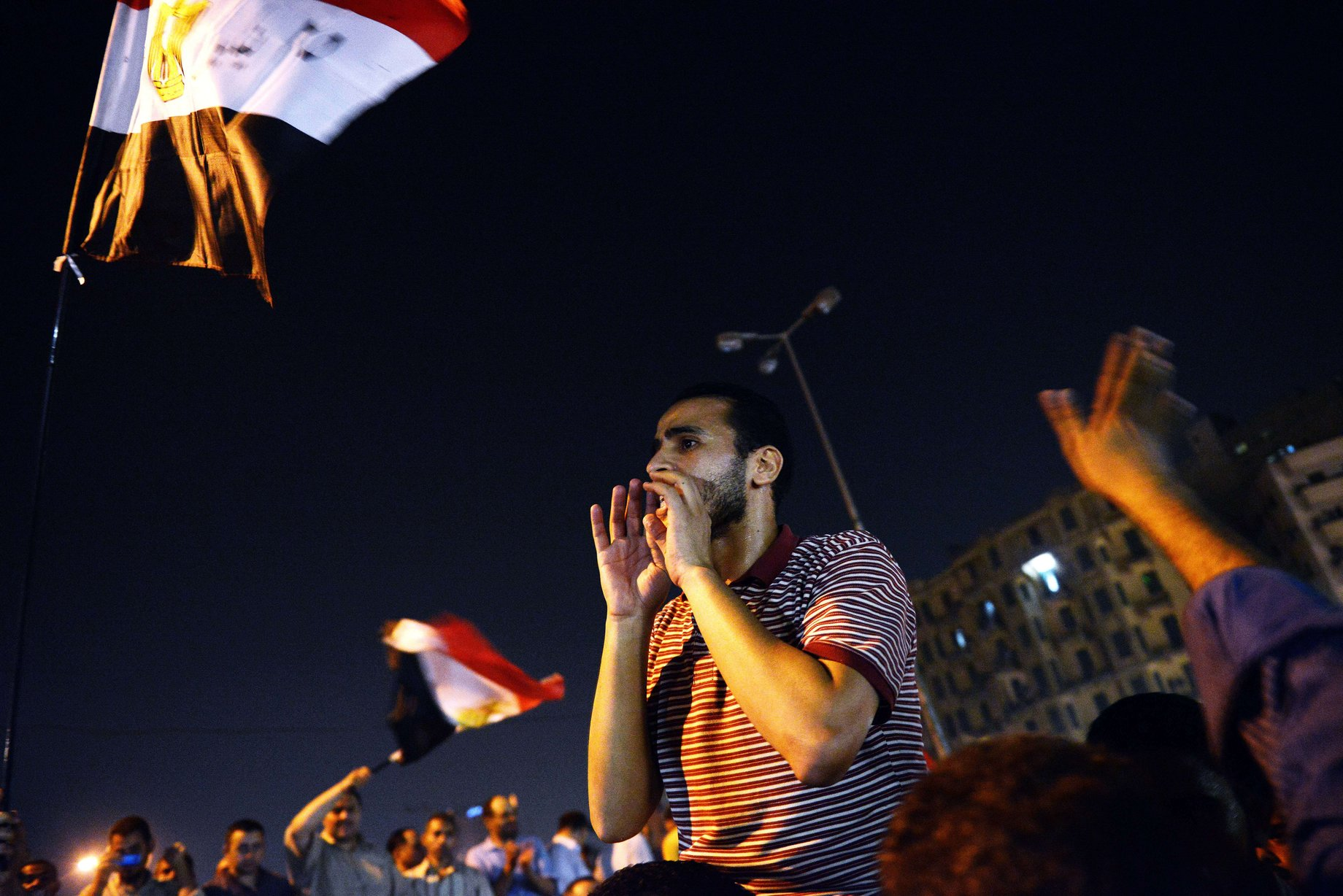 Thousands of Egyptians shout political slogans in support of the Egyptian president Mohamed Morsi as they celebrate his decision on the dismissal of former Egyptian Defence Minister and Field Marshall Hussein Tantawi, on 12 August at Tahrir square in Cairo AFP PHOTO/GIANLUIGI GUERCIA