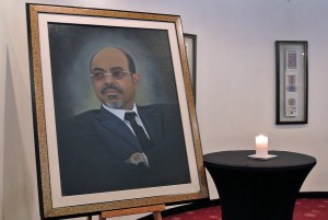 A candle burns beside a mural of late Ethiopia's Prime Minister, Meles Zenawi at a press conference by Ethiopian government spokesman Bereket Simon where he announced the death of Zenawi in Addis Ababa on 21 August