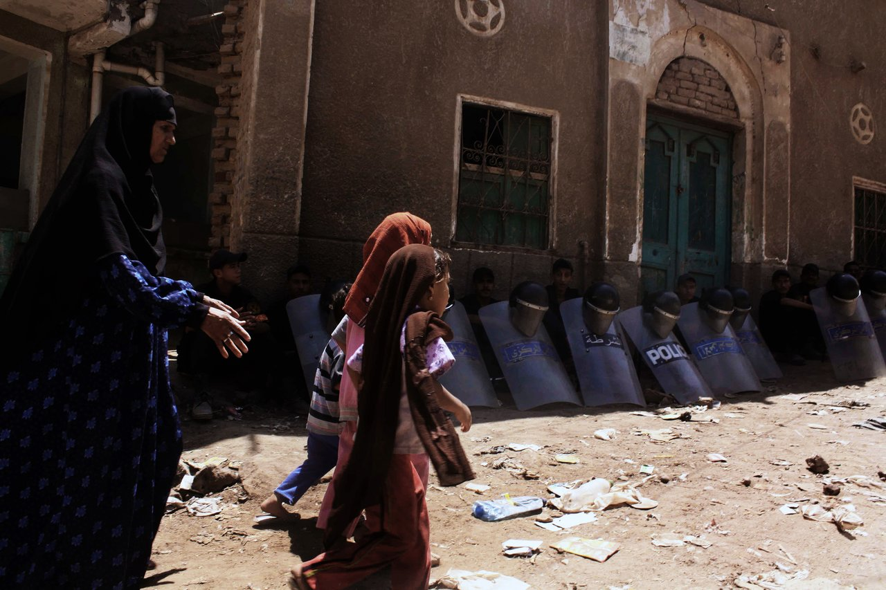 Egyptian riot policemen sit in the shade by damaged buildings on August 2, 2012, as an Egyptian woman and children walk through debris from the aftermath of clashes on August 1, between Christians and Muslims in Dahshur village, on the outskirts of Cairo (file photo: AFP /TAREK EL GABBAS)
