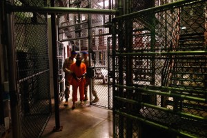 """A """"non-compliant"""" detainee is escorted by guards after showering inside the U.S. military prison for """"enemy combatants"""" on October 27, 2009 in Guantanamo Bay, Cuba (Photo by John Moore)"""