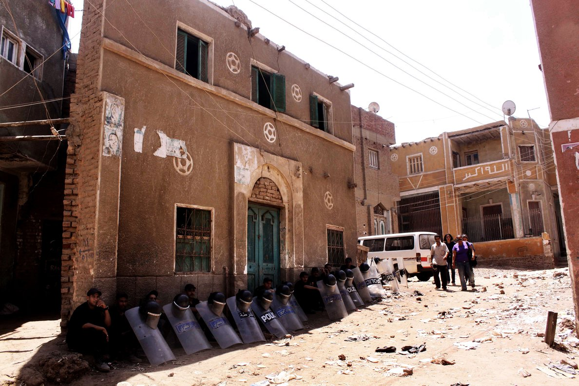 Egyptian riot policemen sit in the shade by damaged buildings on 2 August as people walk through debris from the aftermath of clashes on 1 August between Christians and Muslims in Dahshur village, on the outskirts of Cairo AFP PHOTO/TAREK EL GABBAS
