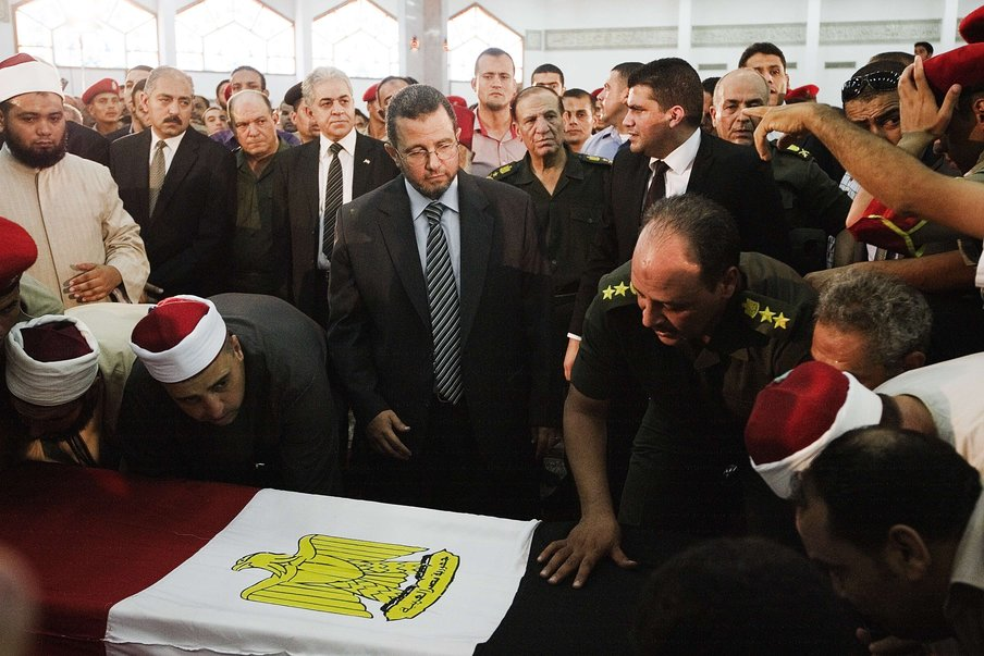 Egyptian Prime Minister Hisham Qandil (C)prepares to lead the prayer over the coffins of the 16 soldiers killed during an attack on a border crossing post in Northern Sinai, during their funeral on August 7, 2012 in Cairo, Egypt-AFP PHOTO/GIANLUIGI GUERCIA
