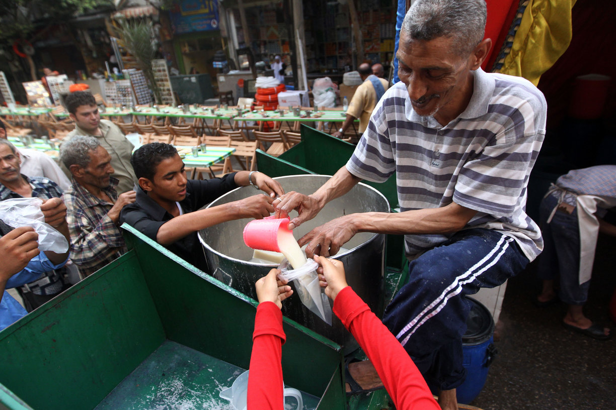 "An Egyptian man distributes free milk for Muslims to break their day-long Ramadan fast during a group ""Iftar"" meal for the residents of a neighbourhood in downtown (File photo) AFP PHOTO / KHALED DESOUKI"