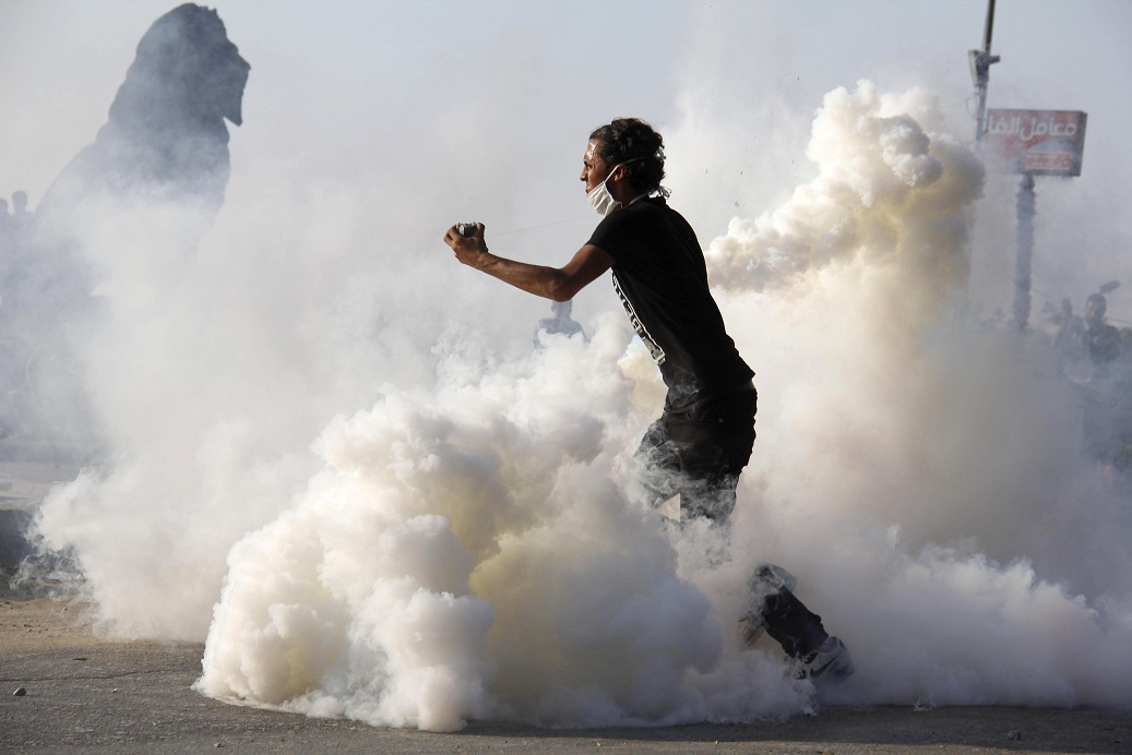 "Protester standing amid a fog of tear gas prepares to throw stones towards policemen during the violence that followed the circulation of clips from the ""Innocence of Muslims"" film AFP PHOTO / MOHAMMED ABDELMONEIM"