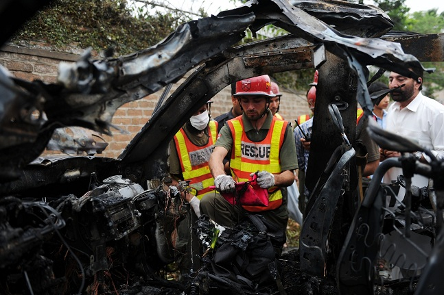 Pakistani rescuers inspect the badly damaged US consulate vehicle at a bomb blast site in Peshawar AFP PHOTO / A MAJEED