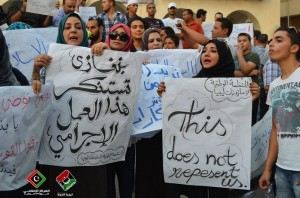"Protesters in Benghazi hold signs denouncing both the ""Innocence of Muslims"" film and the violent reactions to it that lead to the deaths of the US ambassador to Libya and three other US nationals Libyan Tweep Forum"