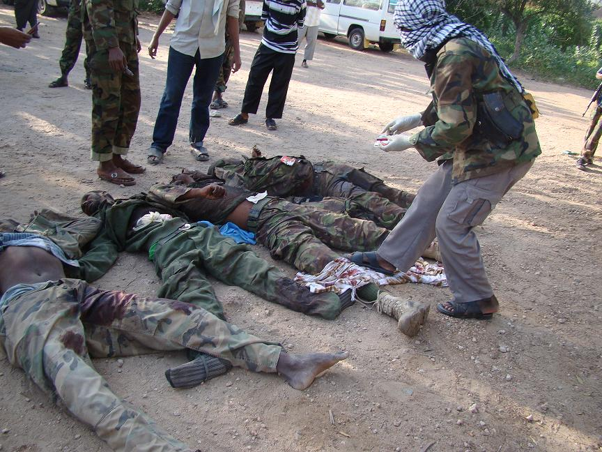 "Photo received on 1 September shows Somalia's Al-Qaeda-linked Shebab militants displaying the bodies of four ""enemy"" soldiers killed in combat in their stronghold of Kismayo, in southern Somalia. AFP PHOTO/HO"