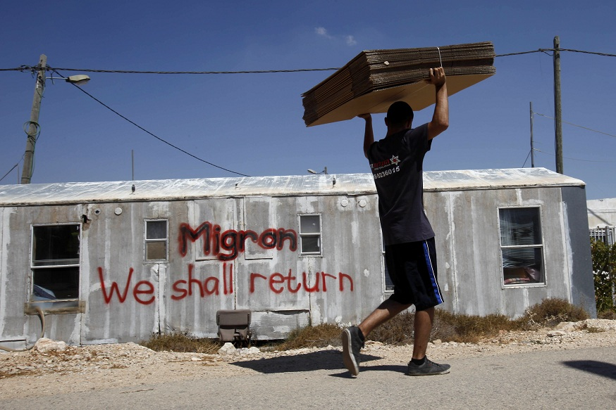 An Israeli moving company employee carries cardboard for boxes as he walks past a caravan of evacuated settlers in the Migron outpost in the occupied West Bank on 2 September AFP PHOTO / GALI TIBBON