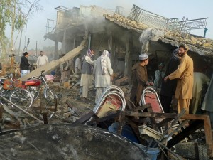 "Afghan men stand at the site of a suicide attack in Kandahar on August 28, 2012. A ""massive"" suicide truck bombing overnight killed four civilians and wounded General Abdul Raziq, the provincial police chief who has a strong anti-Taliban background, authorities said. AFP PHOTO/ JANGIR"