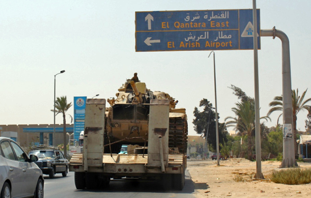 Egyptian tanks are seen being carried on the back of trucks on the Egyptian side of the border city of Rafah on 29 August AFP PHOTO / Stringer