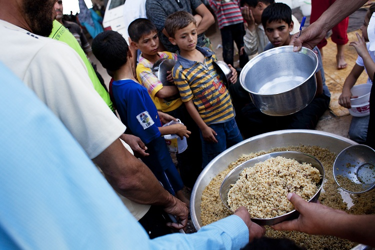 Syrian refugees wait to receive food from a makeshift kitchen in a temporary refugee camp near the Al-Salama crossing between Syrian and Turkey AFP PHOTO / ACHILLEAS ZAVALLIS