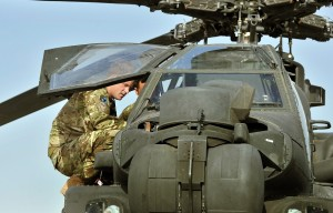 Britain's Prince Harry examines the interior of an Apache helicopter with a member of his 622 Squadron at Camp Bastion in Helmand Province, Afghanistan on 7 September AFP PHOTO / POOL / JOHN STILLWELL
